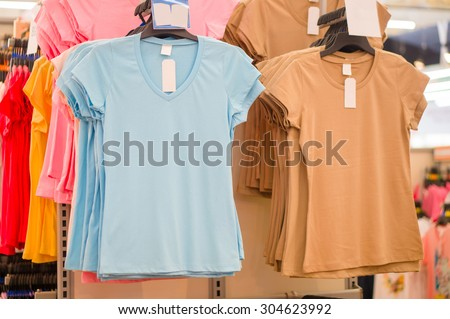 Bunch of blue and brown t-shirts on hangers in supermarket