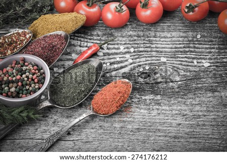 Bunch of cherry tomatoes, herbs, small bowl and antic metal spoons with different kinds of spices, sea salt and red hot chili peppers on old wooden board. Selective focus. Toned. - stock photo