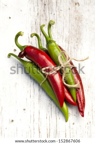 Bunch of Chili Pepper on the old cracked wooden background. - stock photo