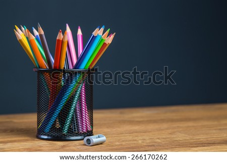 Bunch of color pencils in a stand with sharpener - stock photo