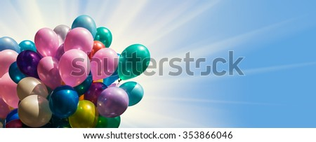 Bunch of colorful balloons against blue sky with sun light - stock photo