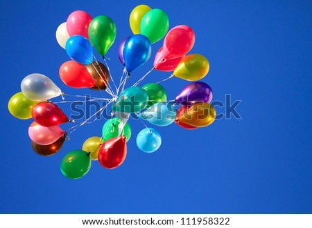 Bunch of colorful balloons floating in the blue sky - stock photo