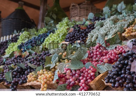 Bunch of Colorful Grapes in Wicker Basket on Wooden Shelf For Sale - stock photo