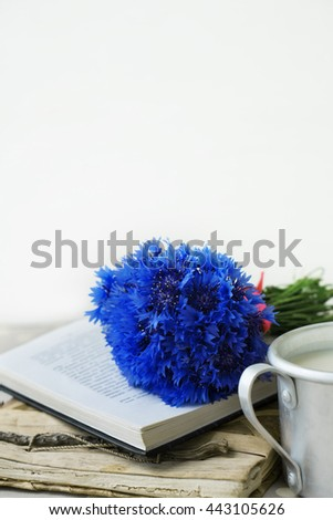 Bunch of cornflowers field and books on an old tablecloth. - stock photo