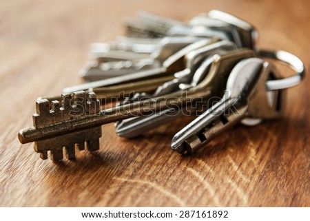 Bunch of different keys on wooden table - stock photo