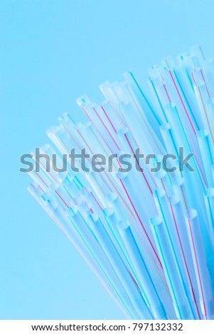 Bunch of drinking straws isolated on a blue background.