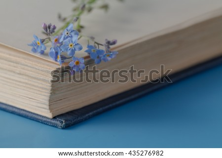 Bunch of forget-me-nots flowers and very old book - stock photo