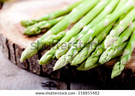 Bunch of fresh asparagus on a wooden background - stock photo