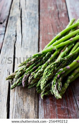 Bunch of fresh asparagus on rustic wooden background. Selective focus. - stock photo