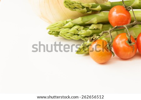 Bunch of fresh asparagus, onion and tomatoes on white background. Vegetable food. - stock photo