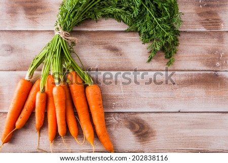 Bunch of fresh carrots with leaves on a rustic background