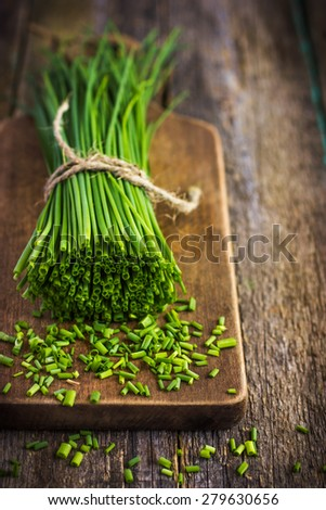 bunch of fresh chives on a wooden cutting board - stock photo