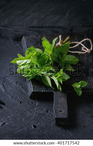 Bunch of fresh mint with thread on black wooden chopping board over black textured background. - stock photo