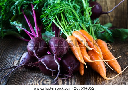 Bunch of fresh organic beetroots and carrots on wooden rustic table - stock photo
