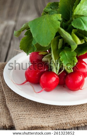 Bunch of fresh organic radish on a rustic wooden background, selective focus - stock photo