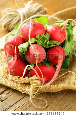 Bunch of fresh organic radishes on a wooden table - stock photo