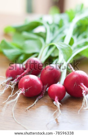 Bunch of fresh radishes on a wooden table - stock photo
