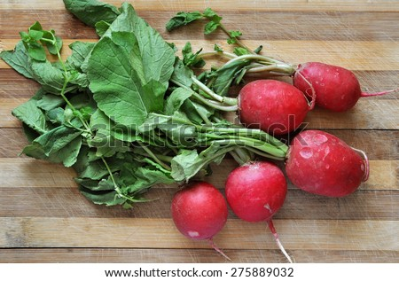 Bunch of fresh radishes on old wooden table - stock photo