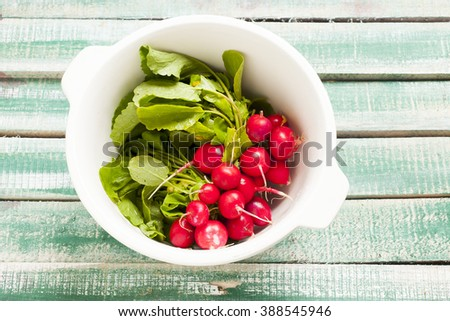 Bunch of fresh radishes on old wooden table wood - stock photo