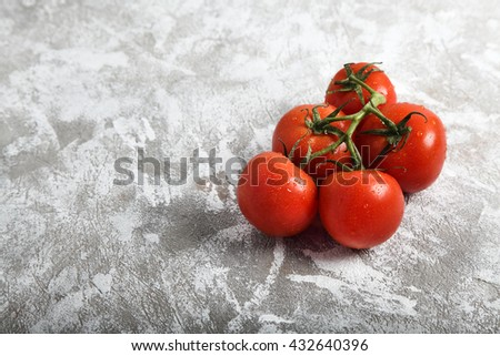 Bunch of fresh red tomatoes for use as cooking ingredients in the foreground with copy space - stock photo