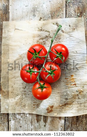 Bunch of fresh red tomatoes in grungy kitchen on a piece of stained, wrinkled oily oven paper on an old wooden tabletop - stock photo