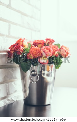 Bunch of fresh roses in a metal bucket for champagne on a table in a bright interior room