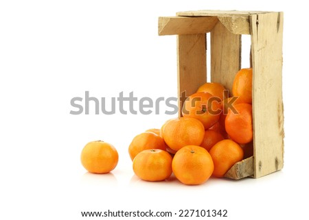 bunch of fresh tangerines in a wooden box on a white background - stock photo