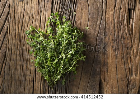 Bunch of fresh thyme sitting on a rustic wooden board. - stock photo