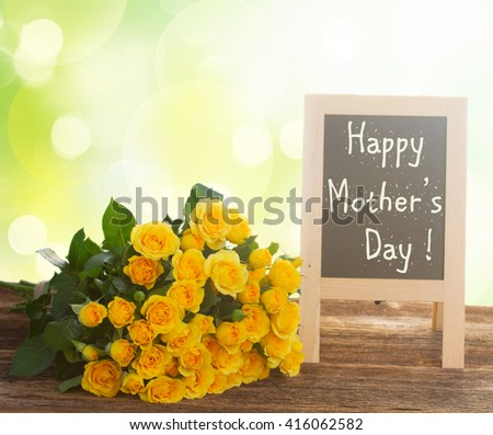 bunch of fresh  yellow roses  with happy mothers day  blackboard on wooden table - stock photo