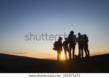 Bunch of friends with backpacks at sunrise/Nature escape - stock photo