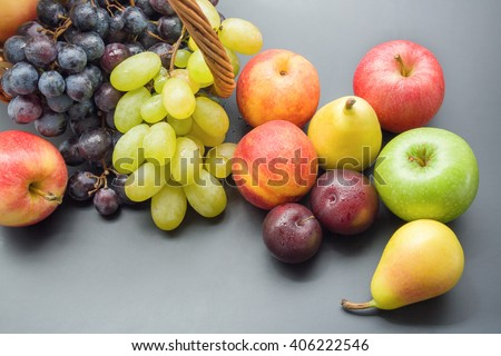 Bunch of fruits. Mix of various fresh ripe fruits top view plums, peaches, pears, apples and grapes on gray neutral background - stock photo