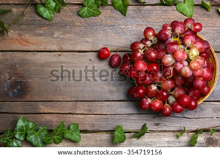 Bunch of grape in wicker bowl and green leaves on wooden background - stock photo