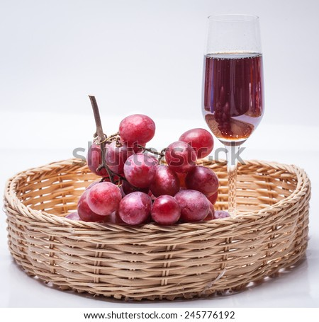 bunch of grapes and a glass of wine in a basket - stock photo