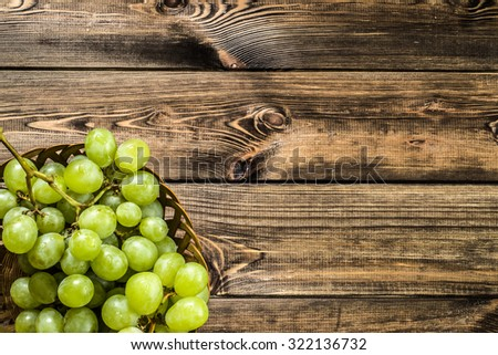 Bunch of green grapes in the basket, fruits of autumn, a symbol of abundance on rustic wood background with copy space, top view, close-up.