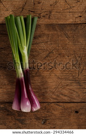 Bunch of green onions on rustic wooden table - stock photo