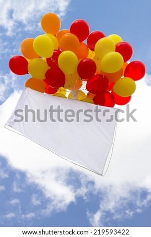 bunch of helium balloons flying in the blue sky and white clouds with a white flag in a frame  - stock photo