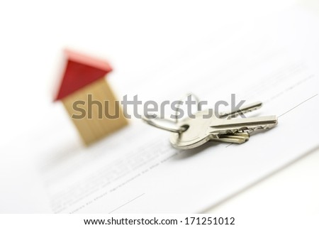 Bunch of house keys lying on a table in front of a small wooden model of a house conceptual of achievement, ownership and security of a property or real estate - stock photo