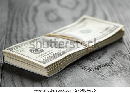 bunch of hundred dollar notes tied with rubberband on wood table - stock photo