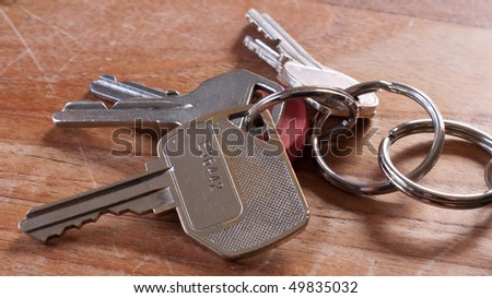 Bunch of keys on wooden table - stock photo