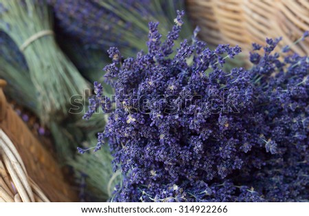 Bunch of lavender flowers on wicker basket. Lavender souvenirs in eco friendly packaging. Photographed in Provence region. - stock photo