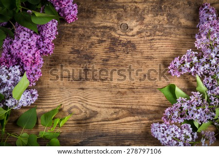 Bunch of lilac on brown wood texture with empty space for text - stock photo