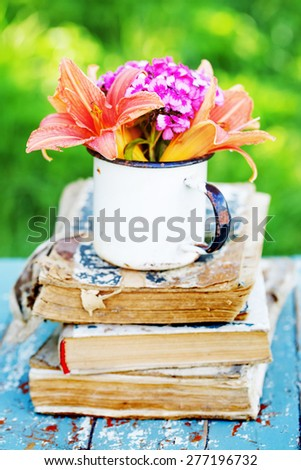bunch of lily flowers on old vintage book in the garden - stock photo