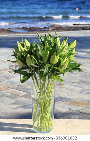 Bunch of lily flowers. Sea background   - stock photo