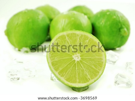 Bunch of limes surrounded by ice cubes isolated on a white background - stock photo