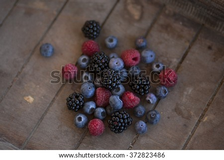 bunch of mixed berries in a wooden basket - stock photo