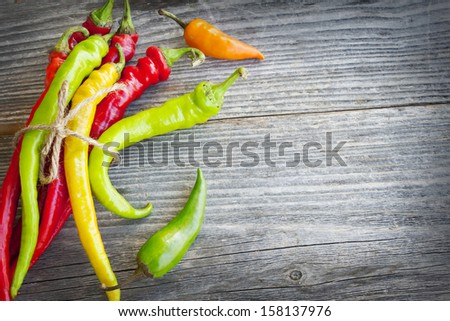 bunch of mixed colored hot chili peppers on wooden textured background - stock photo