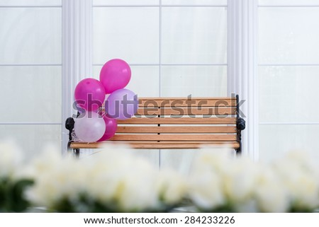 Bunch of multicolored air balloons attached to wooden bench in the white room - stock photo
