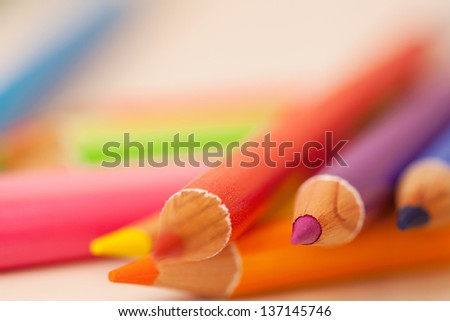 Bunch of multiple colored drawing pencils on a school desk, interior. - stock photo