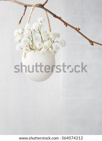 Bunch of of white baby's breath flowers (gypsophila) in egg shell on the white wooden plank. Shallow depth of field, focus on near flowers. Easter decor
