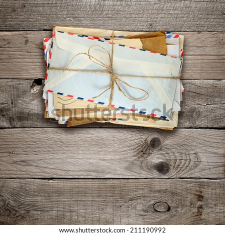 Bunch of old envelopes on wooden background - stock photo